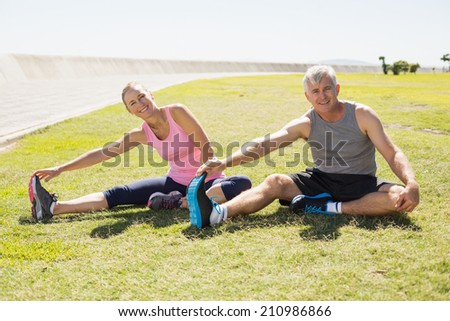 Fit mature couple warming up on the grass on a sunny day - stock photo