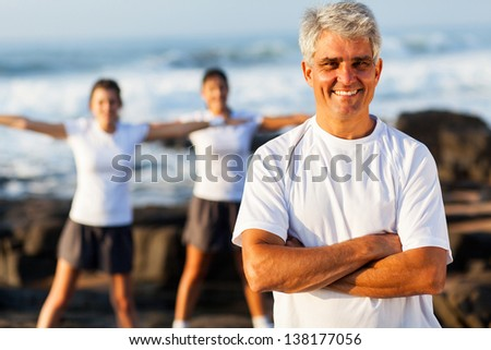 fit mature man on beach with family exercising on background - stock photo