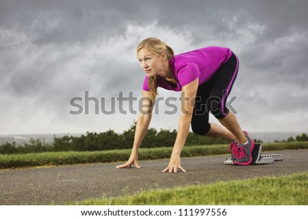 Fit Middle-Aged Female Ready to Sprint - stock photo