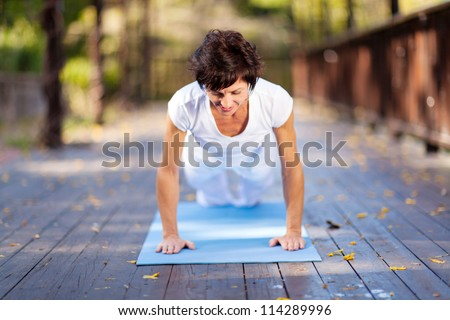 fit middle aged woman doing pushups outdoors - stock photo