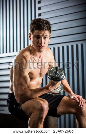 Fit muscular man exercising with a dumbbell - stock photo