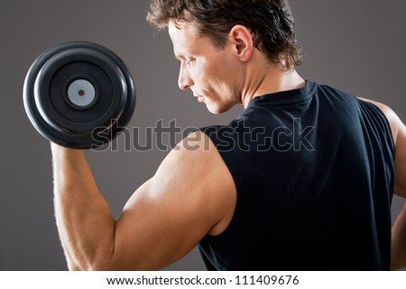 Fit muscular man exercising with dumbbell on gray background