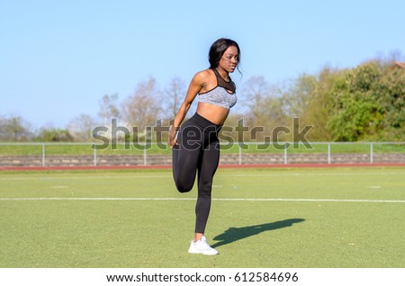 Fit muscular young African woman doing warming up exercises stretching her muscles before doing a sports workout on a track