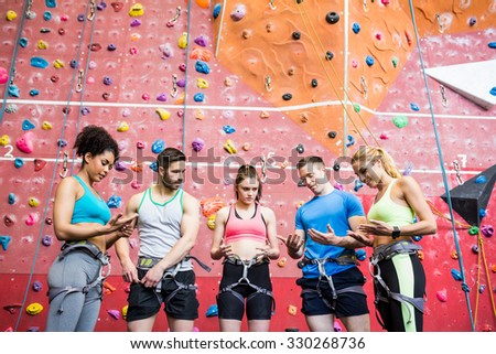 Fit people getting ready to rock climb at the gym - stock photo