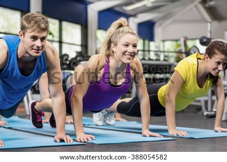 Fit people in plank position in gym - stock photo