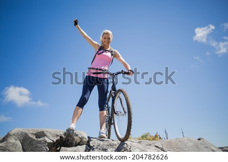 Fit pretty cyclist on a rocky terrain smiling at camera on a sunny day