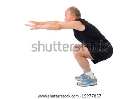 Fit senior man doing a squat - stock photo