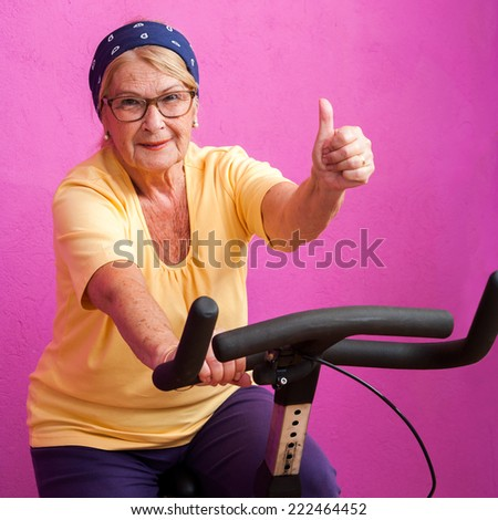 Fit senior woman doing thumbs up on at spinning session in gym. - stock photo