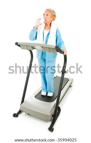 Fit senior woman working out on a treadmill, taking a break to stay hydrated.