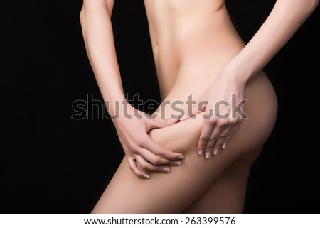 Fit sexy woman holding showing cellulite area.Woman pinches her thigh to control cellulite.Plastic surgery,healthy nutrition,fat lose,liposuction,healthy lifestyle sport and cellulite removal concept - stock photo