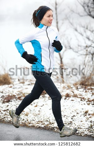 Fit slender young woman taking her daily exercise out jogging in a snowy landscape in winter - stock photo