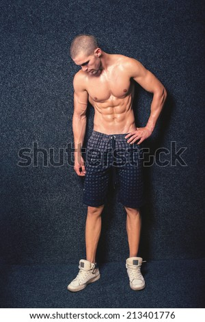 Fit slim muscular shirtless young man posing against dark background. Fitness guy looking down posing showing his muscular torso and abdomen.  - stock photo