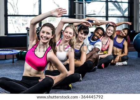 Fit smiling group doing exercise in gym