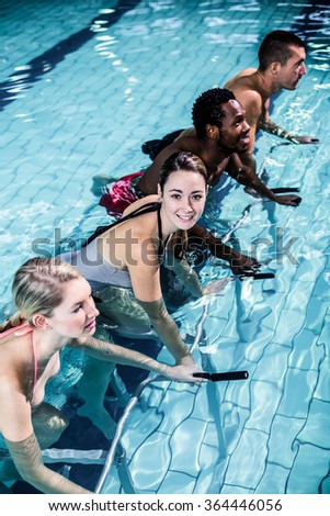 Fit smiling group pedaling on swimming bike in pool - stock photo