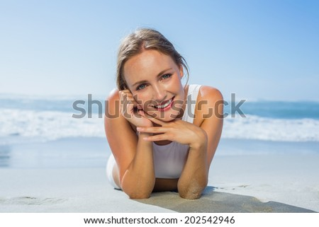 Fit smiling woman lying on the beach on a sunny day - stock photo