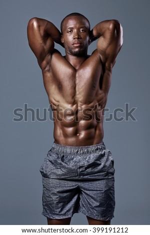 Fit strong black man with sexy lean body posing in studio