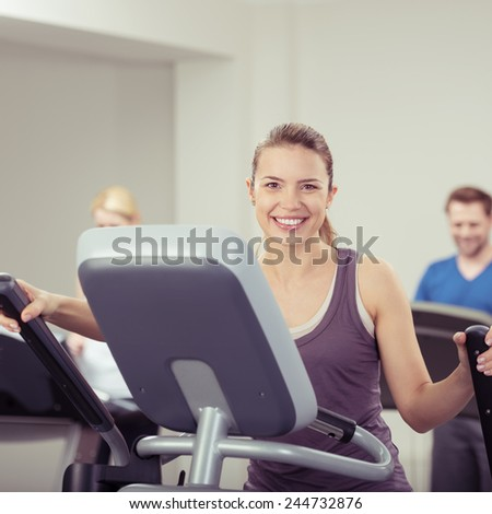 Fit vivacious young woman at the gym working out on the equipment while looking at the camera with a warm friendly smile - stock photo