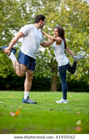 Fit woman and her sports trainer stretching outdoors - stock photo
