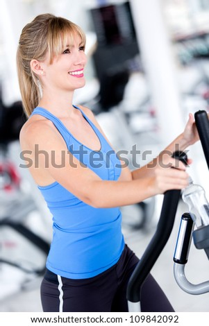 Fit woman at the gym exercising looking happy - stock photo