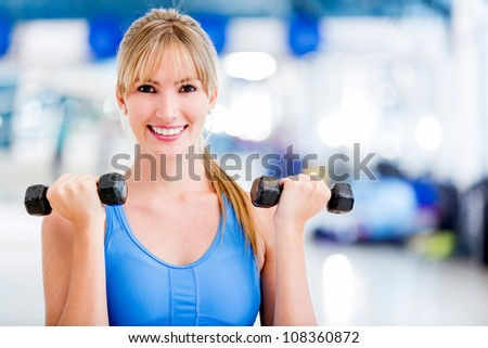 Fit woman at the gym lifting weights - stock photo