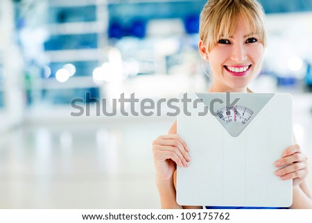 Fit woman checking her weight on a scale - stock photo