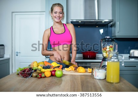 Fit woman cutting fruits in the kitchen - stock photo