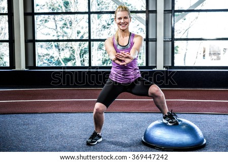 Fit woman doing exercise with bosu ball in crossfit - stock photo