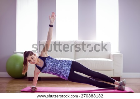 Fit woman doing side plank at home in the living room - stock photo