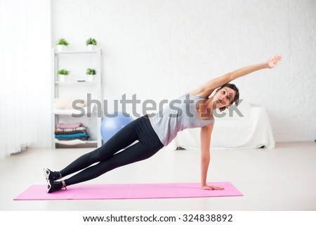 Fit woman doing side plank yoga pose at home in the living room on mat Concept pilates fitness healthy lifestyle - stock photo