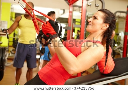 Fit woman doing TRX suspension training workout in gym. - stock photo