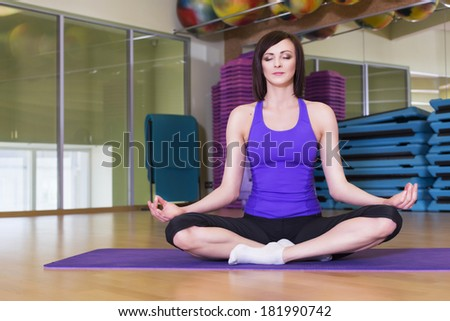 Fit Woman doing yoga exercise on a Mat in a Gym smiling - stock photo