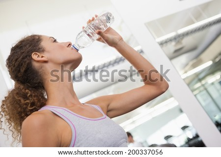 Fit woman drinking from water bottle at the gym - stock photo