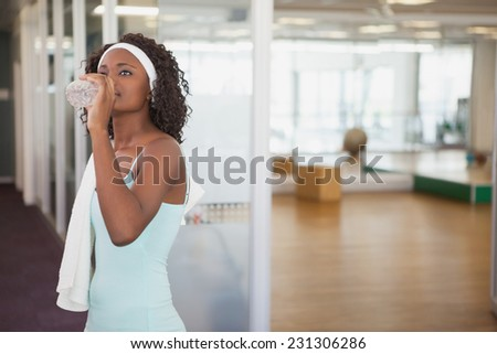 Fit woman drinking water in fitness studio at the gym - stock photo