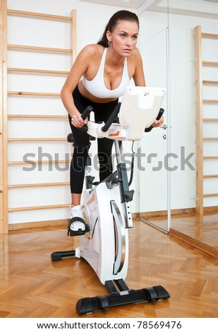 fit woman driving stationary bicycle in gym - stock photo