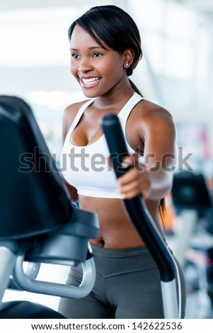 Fit woman exercising at the gym on an x-trainer - stock photo