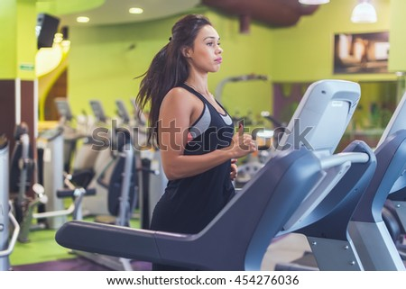 Fit woman exercising on treadmill in gym. - stock photo