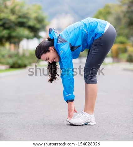 Fit woman exercising outdoors stretching and looking happy