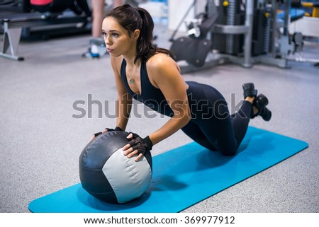 Fit woman exercising with medicine ball workout out arms Exercise training triceps and biceps doing push ups. - stock photo