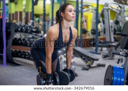 Fit woman fitness performing doing deadlift exercise with dumbbell - stock photo