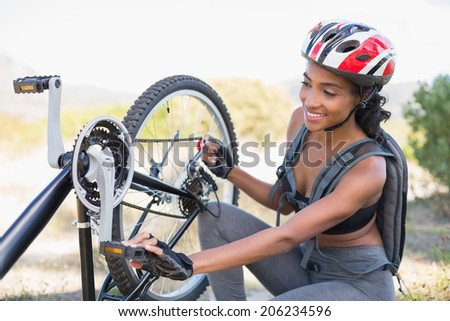 Fit woman fixing the chain on her bike on a sunny day in the countryside