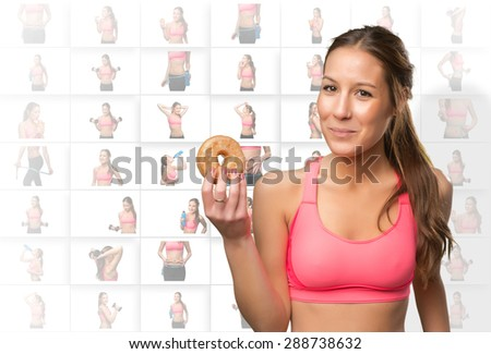 Fit woman holding a donut - stock photo