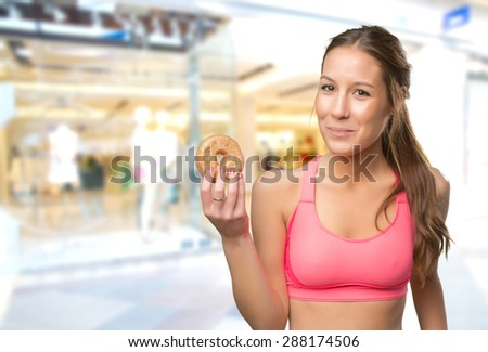 Fit woman holding a donut. Over shopping center background - stock photo