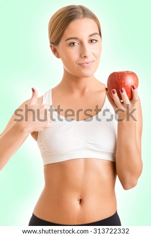 Fit woman holding and apple and giving a thumbs up
