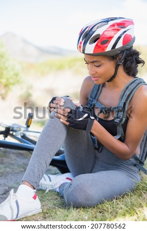 Fit woman holding her injured knee after bike crash on a sunny day in the countryside - stock photo