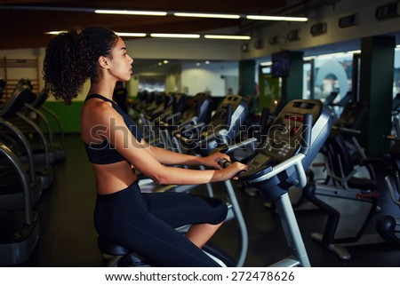 Fit woman in a spin class at gym, attractive girl with afro hair spinning on simulator bicycle equipment at fitness center - stock photo