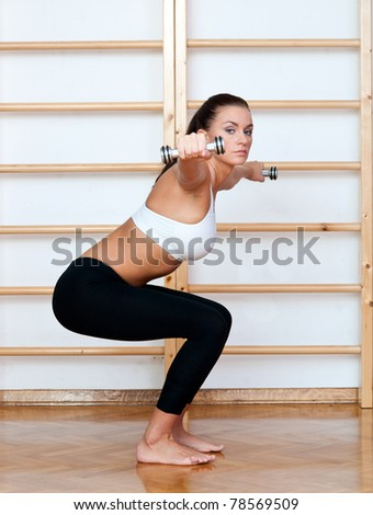 fit woman in fitness pose with weights in gym - stock photo