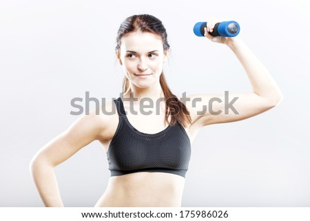 Fit woman in sport bra during exercise with dumbbells