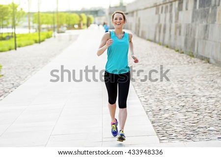 Fit woman jogging in park. - stock photo