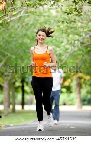 Fit woman jogging outdoors at the park - stock photo