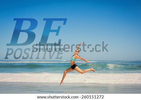 Fit woman jumping gracefully on the beach against be postive - stock photo